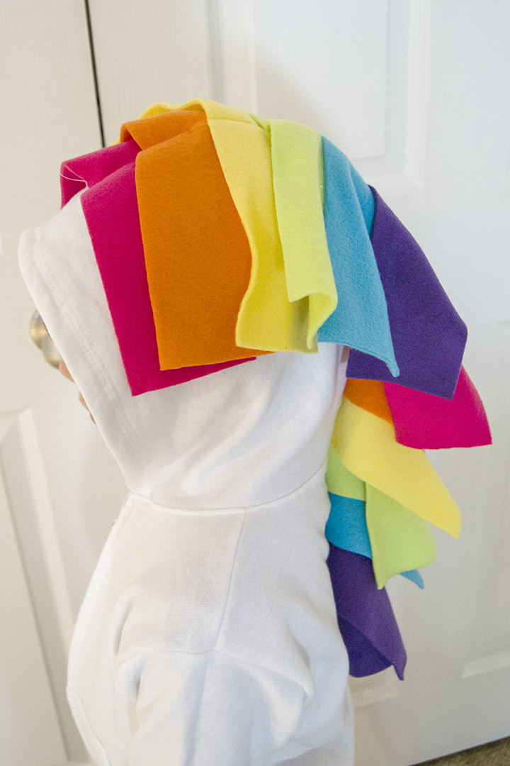 Use fleece strips to make a unicorn mane and tail on a DIY unicorn hoodie costume.