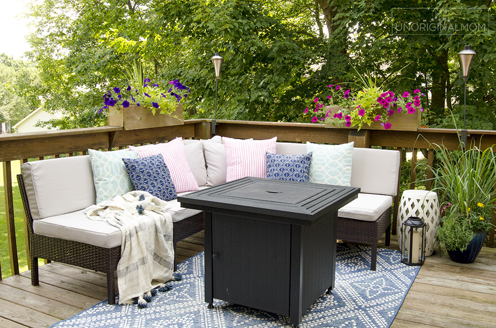 Small outdoor sectional with throw pillows and a gas fire pit on a deck | small deck decorating ideas